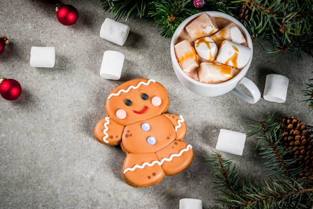 Traditional christmas treat. hot chocolate with marshmallow, gingerbread man cookie, fir tree branches and xmas holiday decorations  copyspace top view
