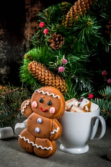 Traditional christmas treat. hot chocolate with marshmallow, gingerbread man cookie, fir tree branches and xmas holiday decorations  copyspace