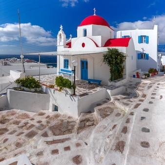 Традиционная церковь с красным куполом и побеленным фасадом, типичное греческое церковное здание на острове миконос, остров ветров, греция