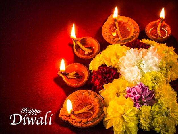 Traditional clay diya lamps lit with flowers for diwali festival celebration.