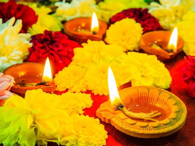 Традиционные глиняные лампы diya, освещенные цветами для празднования фестиваля дивали