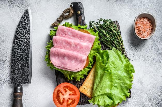 ターキーハム、チーズ、トマト、レタスの伝統的なクラブサンドイッチ。白色の背景。上面図。