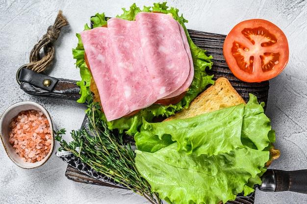 Традиционные клубные бутерброды с ветчиной из индейки, сыром, помидорами и листьями салата. белый фон. вид сверху.
