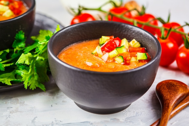 Traditional cold gazpacho tomato soup in black bowl on a gray