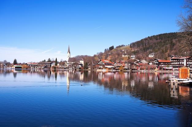 Традиционные красочные дома, украшенные цветами и церковная башня в альпийской деревне, гальштат, австрия