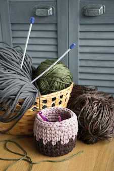 Traditional colorful yarns for hobby knitting in a straw eco basket on a light wooden surface.