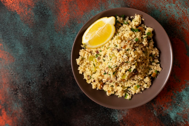 Традиционный кускус с овощами и зеленью в миску. левантинский вегетарианский салат. ливанская, арабская кухня. вид сверху. копировать пространство