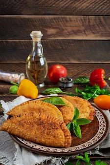 전통적인 크림 타타르 요리, 닭고기를 곁들인 체부레키. 나무 배경에 튀긴 엠파나다