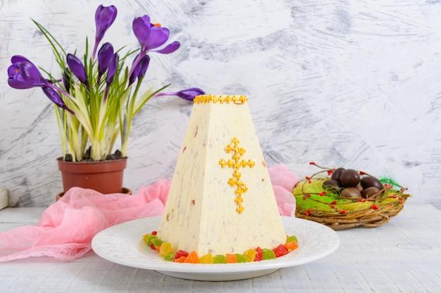 砂糖漬けの果物とチョコレートの卵、伝統的な豆腐イースターケーキ、休日明るい背景に春の花クロッカス。