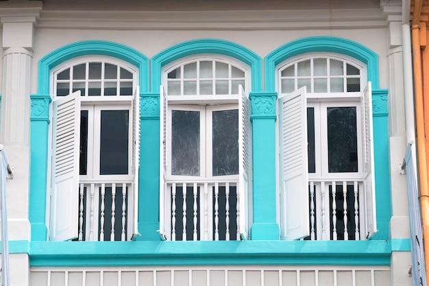 Традиционно оформленные окна с деревянными ставнями старого здания в китайском квартале сингапура