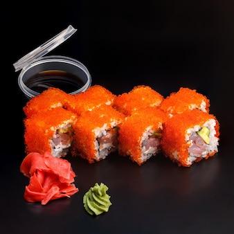 Традиционный вкусный свежий суши-ролл california king на черной поверхности Premium Фотографии