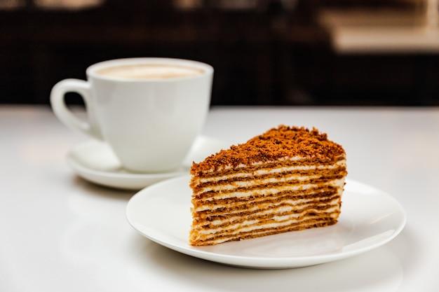 Традиционный вкусный медовый торт и чашка кофе