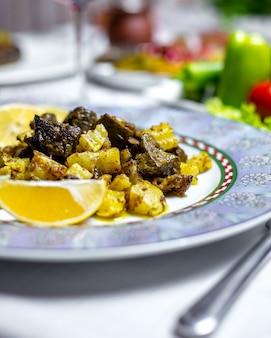 Vista laterale del limone dell'olio delle fette della patata delle patatine fritte agnello del fegato fritte bizz del djizz del piatto tradizionale