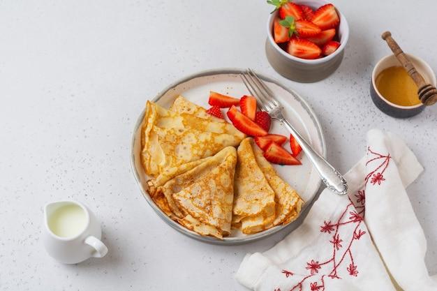 휴일 maslenitsa의 전통 요리. 꿀, 신선한 딸기 및 아침 식사를 만들기위한 재료로 만든 얇은 크레이프 팬케이크. 평면도.