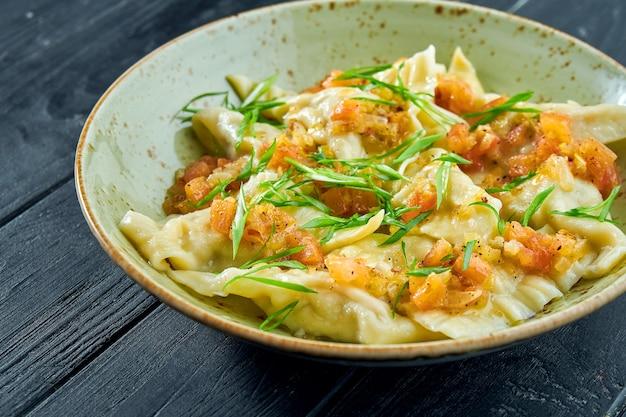 Традиционное блюдо израильской кухни - куриный креплач с томатной сальсой и зеленым луком в тарелке на черной деревянной поверхности. ресторанная еда. вареники с разными начинками