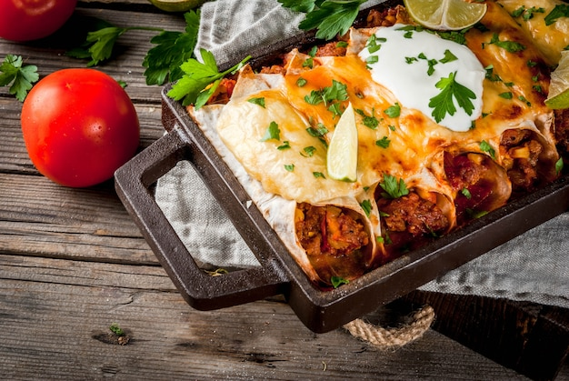 Traditional dish of spicy beef enchiladas with corn, beans, tomato. on a baking tray