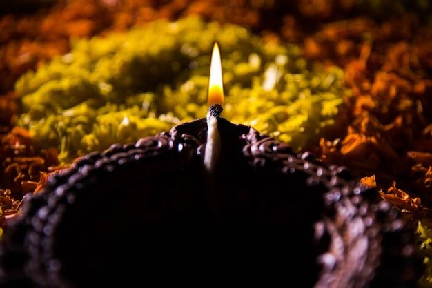 Традиционная дия или масляная лампа, освещенная на красочных ранголи, составленных из цветочных лепестков, на фестивале огней, называемом дивали или дипавали, выборочный фокус