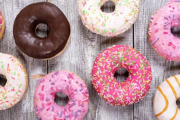 Традиционные пончики с разноцветной глазурью, изложенные на белом фоне окрашенные деревянные крупным планом.