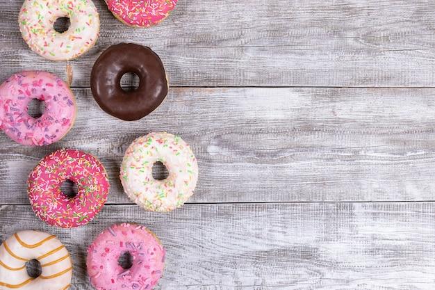 Традиционные пончики с разноцветной глазурью выложены на белый расписной деревянный стол. вид сверху, скопируйте пространство.