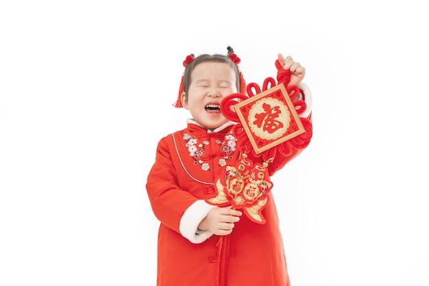 彼女の手に伝統的なペンダントを持つ中国の女の赤ちゃんの伝統的なドレス