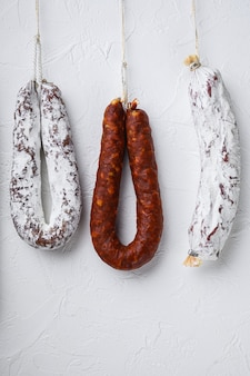 Traditional dry cured sausages meat hanging on white surface.