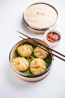 네팔의 전통 만두 모모스 음식은 변덕스러운 배경 위에 토마토 처트니와 함께 제공됩니다. 선택적 초점