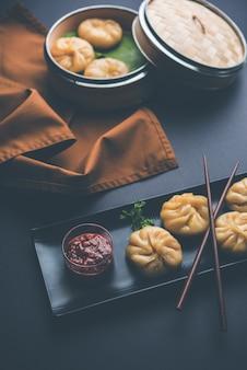 Традиционная еда момо с клецками из непала подается с томатным чатни на унылом фоне. выборочный фокус
