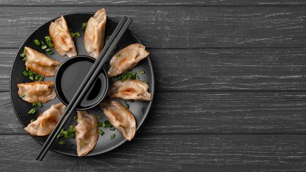 Традиционные пельмени на тарелке с палочками для еды