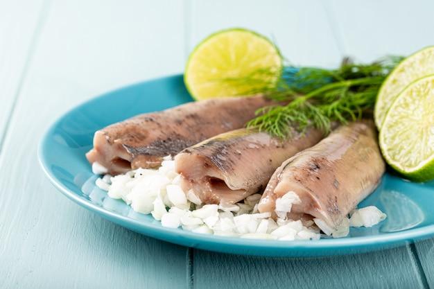 Традиционные голландские блюда из свежесоленой сельди с луком под названием hollandse nieuwe на бирюзовой тарелке и деревянной поверхности. европейская концепция питания с копией пространства
