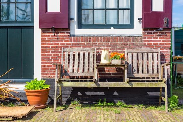 Zaanse schans 마을, 네덜란드에있는 나무 벤치와 꽃이있는 전통적인 네덜란드 집. 유명한 관광 장소.