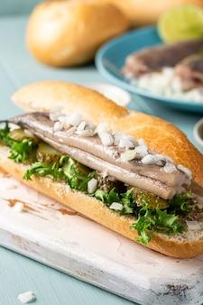 伝統的なオランダのスナック、ニシン、玉ねぎ、きゅうりのピクルスを添えたシーフードサンドイッチ。 broodjeharing。閉じる
