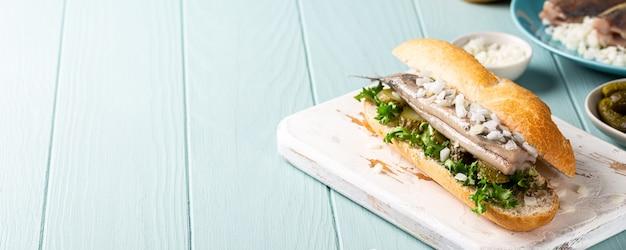 伝統的なオランダのスナック、ニシン、玉ねぎ、きゅうりのピクルスを添えたシーフードサンドイッチ。 broodje haring、コピースペース、バナー