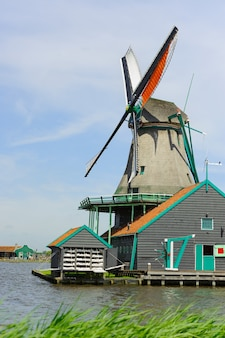 Traditional dutch windmill near the canal in summer day. netherlands