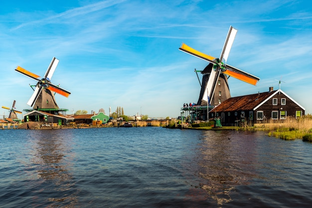 Traditional dutch windmills located by the river zaan, in zaanse schans, netherlands.