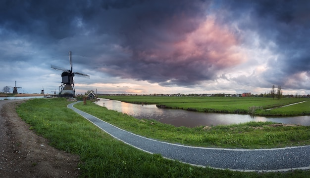 Traditional dutch windmills near water canals with cloudy sky, landscape