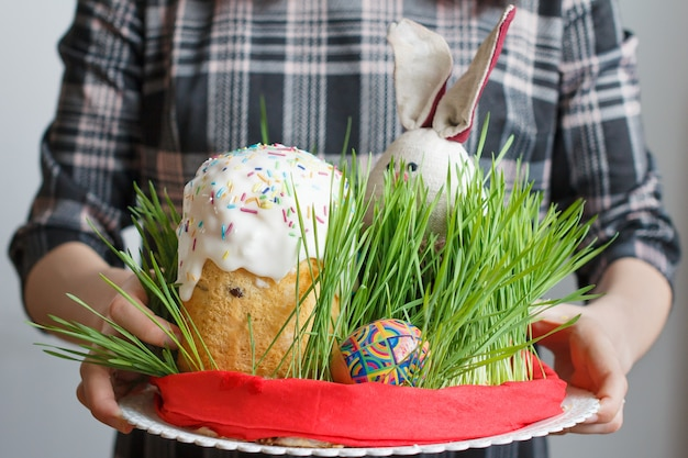 Traditional easter cake, eggs and bunny in the grass in womans hands.