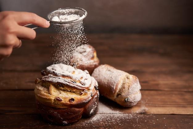 伝統的なイースターケーキクラフィンは、暗い背景に木製のテーブルの上に立っています。コピースペースのある春休みパン料理人に粉砂糖をまぶす