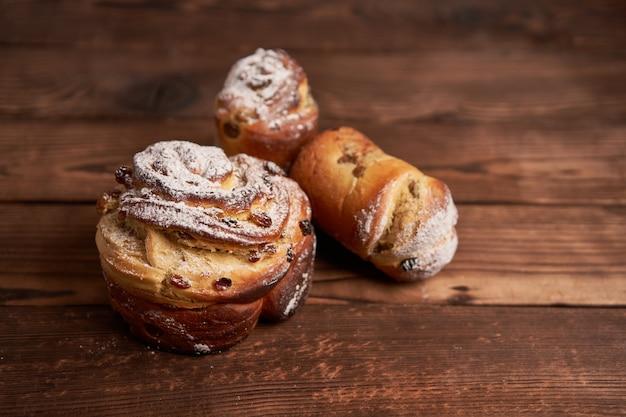 伝統的なイースターケーキクラフィンは、暗い背景に木製のテーブルの上に立っています。コピースペース付き春休みパン