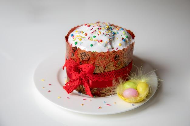 白いプレートに赤いリボンと伝統的なイースターケーキ