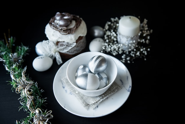 Traditional easter cake with silver painted eggs, candles and willow on a black surface. selective focus