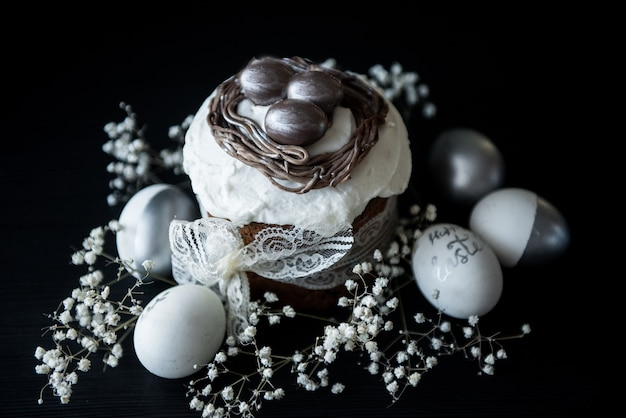 Traditional easter cake with silver painted eggs, candles and willow on a black table. selective focus