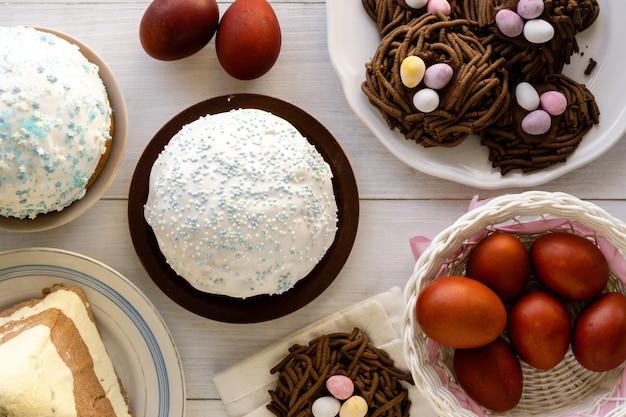 伝統的なイースターフード。木製のテーブルにケーキ、ネストクッキー、色付きの卵。
