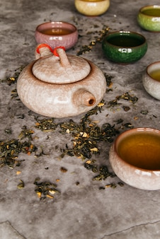 Traditional eastern teapot and teacups on concrete background
