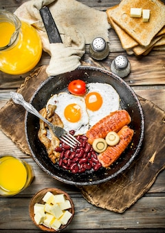 Traditional english breakfast. appetizers with fried bread and orange juice on wooden table.