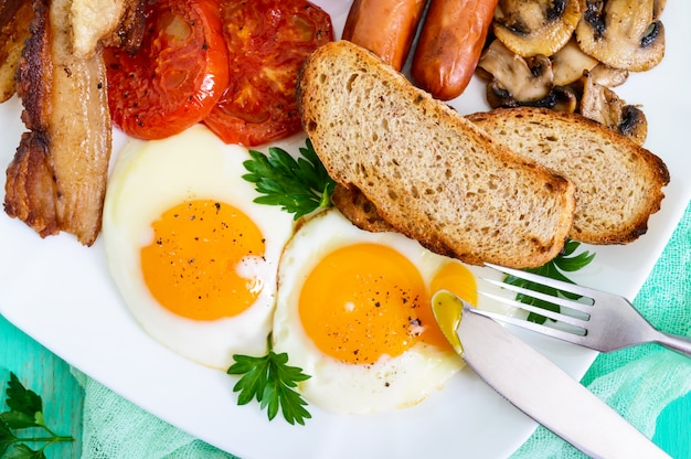 Традиционный английский завтрак: бекон, грибы, яйца, помидоры, колбаски, бобы, тосты на белой тарелке на ярком деревянном столе. классическая английская кухня. закройте вид сверху