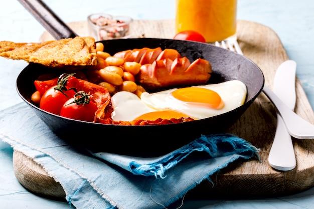 Traditional english breakfast . eggs heart shape.