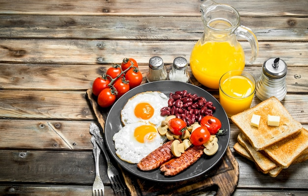 전통적인 영국식 아침 식사. 콩, 소시지, 튀긴 빵과 함께 튀긴 계란. 나무 배경.