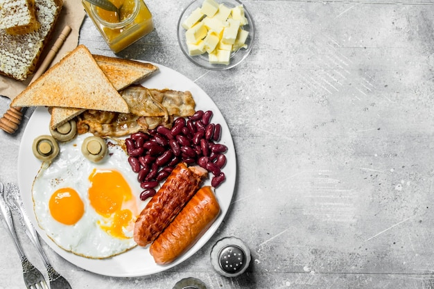 Traditional english breakfast. fried eggs with sausages and fried bread. on a rustic table.