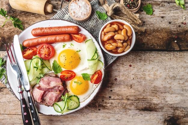 Традиционный английский завтрак с яичницей, беконом, фасолью, кофе и колбасой на деревянной поверхности, вид сверху