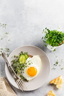 Traditional english breakfast with fried eggs in ceramic plate on gray concrete background